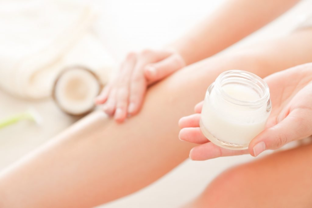 woman applying CBD body butter on her legs